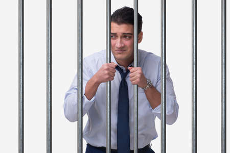 Young businessman behind the bars in prison Stock Photo