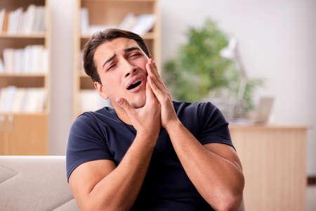 Junger stattlicher Mann mit Schmerzen Standard-Bild - 69339931