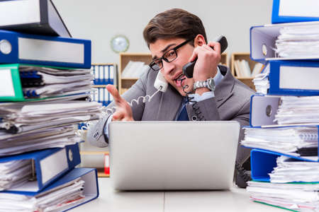 Ocupado hombre de negocios bajo estrés debido al exceso de trabajo Foto de archivo