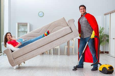Superhero husband helping his wife at home Imagens