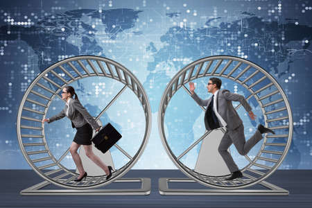 Business concept with pair running on hamster wheel