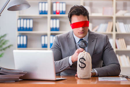 Blindfold businessman sitting at desk in office Stock Photo