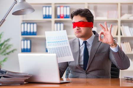 Blindfold hombre de negocios sentado en el escritorio en la oficina Foto de archivo