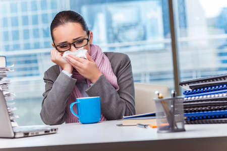 Young businesswoman sick in the office Stock Photo