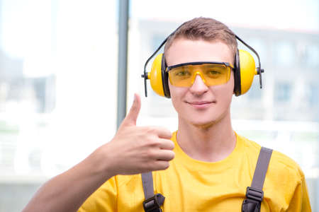 Young construction worker in yellow coveralls Stock Photo