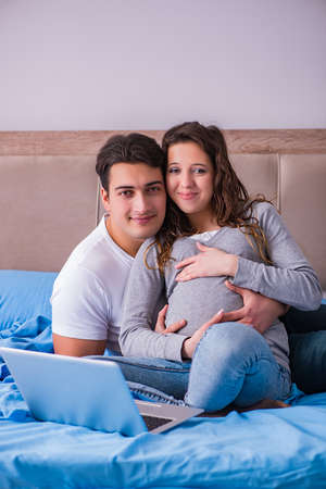 Young family with pregnant wife expecting baby in bed Stock Photo