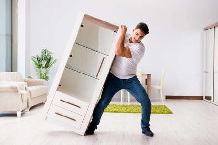 Jonge man het verplaatsen van meubilair thuis