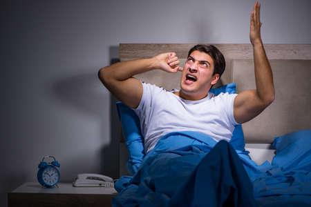 Jonge man die worstelt met lawaai in bed
