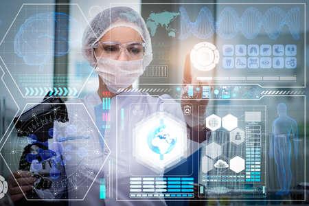 Doctor in futuristic medical concept pressing button Foto de archivo
