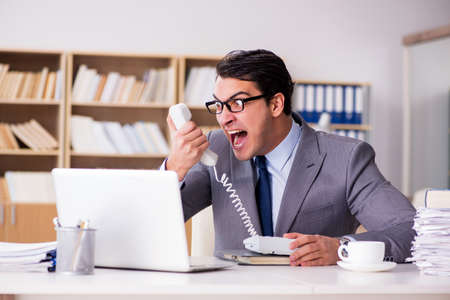Uomo d & # 39 ; affari arrabbiato che lavora in ufficio