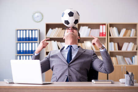 Businessman with football ball in office Stock Photo