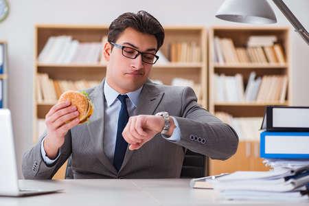 Hongerige grappige zakenman het eten van junk food sandwich