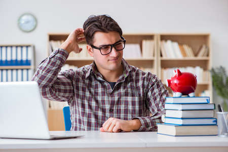 Student breaking piggybank to pay for tuition fees Stock Photo