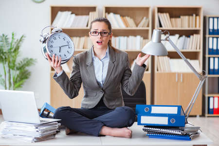 Empresaria con reloj de alarma en la oficina Foto de archivo - 76179458
