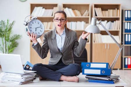 Geschäftsfrau mit Wecker im Büro Standard-Bild - 76179458