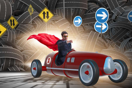 Superhero businessman driving vintage roadster Stock Photo