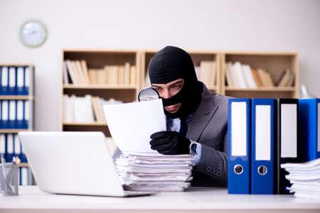 Criminal businessman wearing balaclava in office Stock Photo