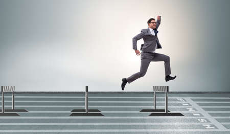 Businessman jumping over barriers in business concept Zdjęcie Seryjne - 77825620