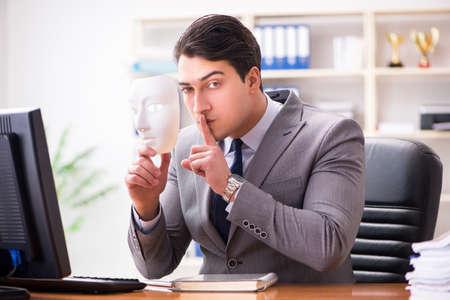 オフィス偽善コンセプトのマスクを持ったビジネスマン 写真素材