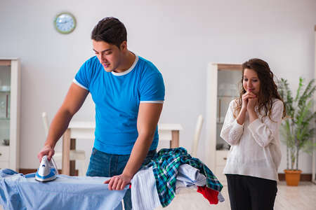 Man husband ironing at home helping his wife Stock Photo