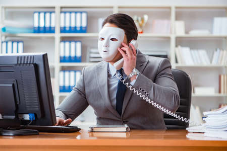 Businessman with mask in office hypocrisy concept 스톡 콘텐츠