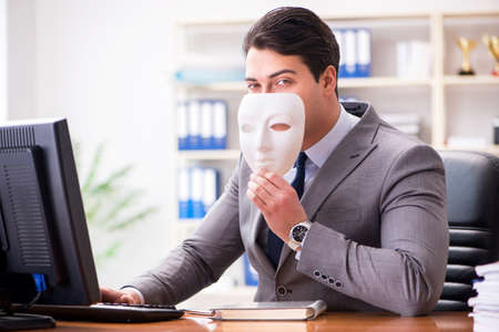 Businessman with mask in office hypocrisy concept Stock Photo