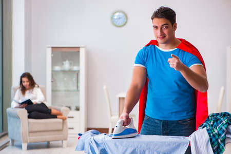Super hero man husband ironing at home helping his wife Stock Photo