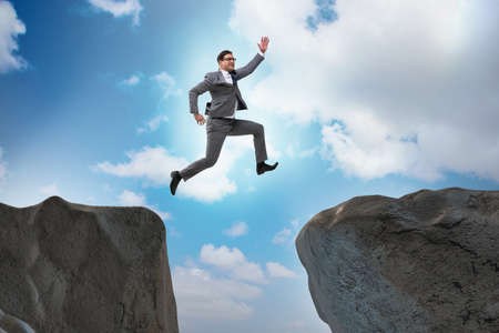 Ambitious businessman jumping over the cliff