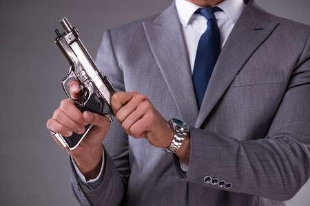 주머니에서 총을 당기는 사업가