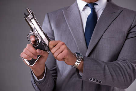 Businessman pulling the gun out of pocket Zdjęcie Seryjne - 79633656