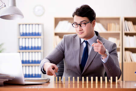 Businessman with dominoes in the office Stock Photo
