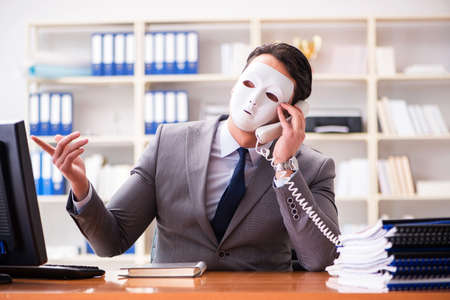 Businessman with mask in office hypocrisy concept Stockfoto