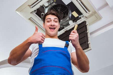 Werknemer reparatie van plafond airco unit