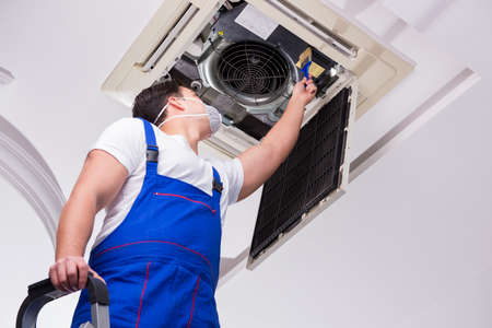 Worker repairing ceiling air conditioning unit Stock Photo