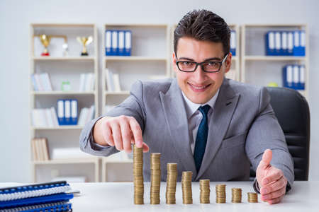 Businessman with golden coins in business growth concept Stock Photo
