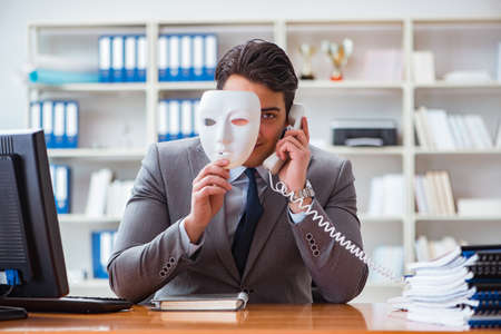 Businessman with mask in office hypocrisy concept Foto de archivo