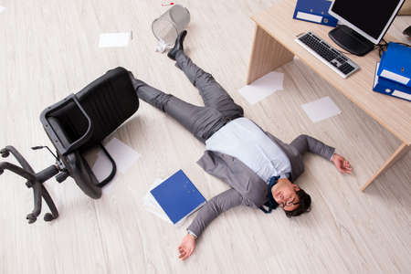 Businessman dead on the office floor 版權商用圖片