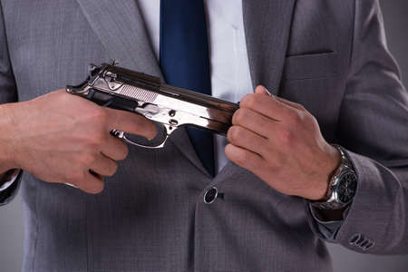 Businessman pulling the gun out of pocket Stock Photo - 80904035