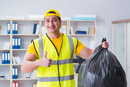 Man cleaning the office and holding garbage bag Stock Photo