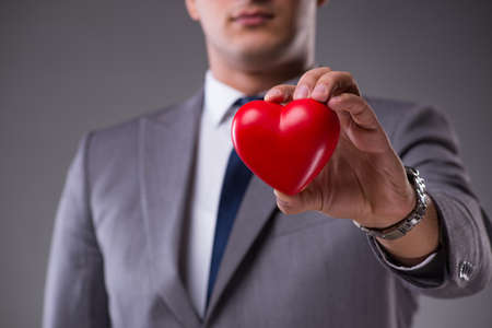 Businessman holding red heart in love concept Stock Photo