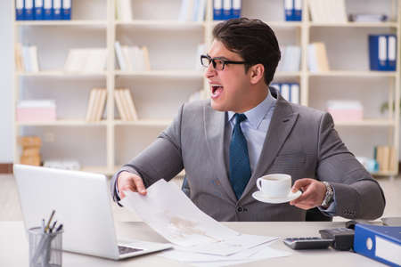 Businessman spilling coffee on important documents Stock Photo