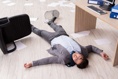 Businessman dead on the office floor Stock Photo