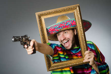 Man in a vivid mexican poncho gray background isolated Stock Photo