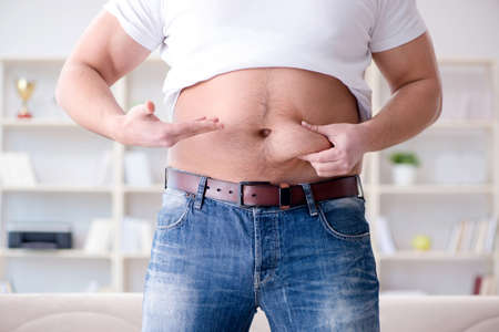Man suffering from extra weight in diet concept Foto de archivo