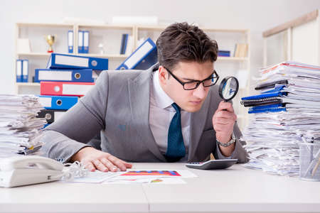 Mannelijke zakenman met vergrootglas in kantoor