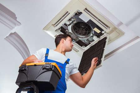 Worker repairing ceiling air conditioning unit Standard-Bild