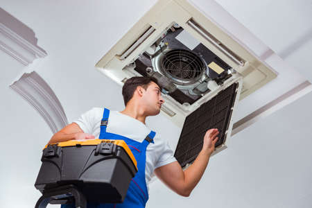Worker repairing ceiling air conditioning unit Imagens