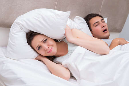 Woman having trouble with husband snoring Foto de archivo