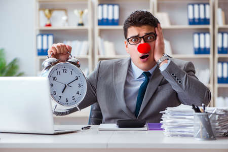 Clown businessman with alarm clock missing dieadline Stock Photo