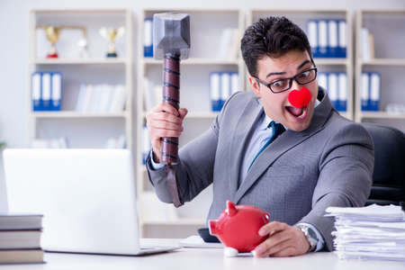 Clown businessman with a piggy bank and a hammer Archivio Fotografico